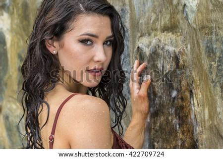 Young brunette model posing against a waterfall - stock photo