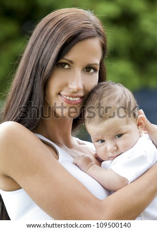 young brunette modther holding her baby girl outdoors