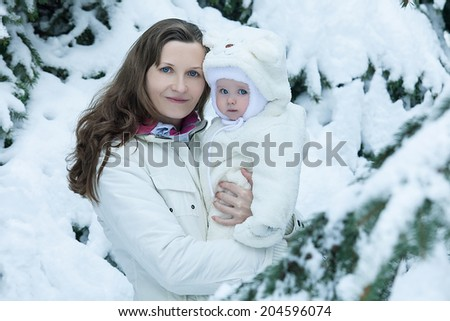 Young brunette mother with her daughter outdoors in park - stock photo