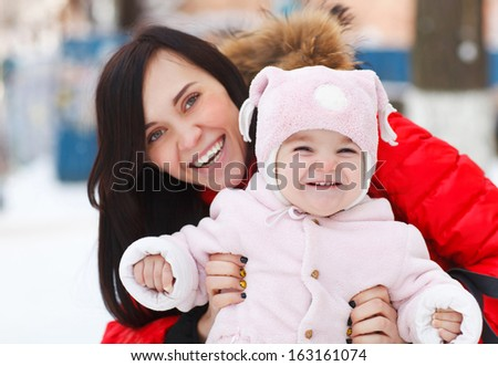 Young brunette mother with her daughter outdoors. Winter