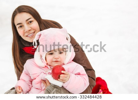 Young brunette mother with her daughter outdoors. Winter - stock photo
