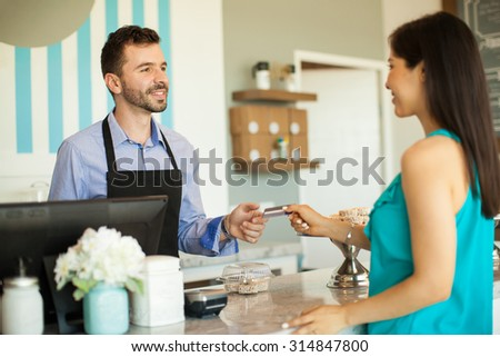 Young brunette paying with a credit card at the cash register in a cake shop - stock photo