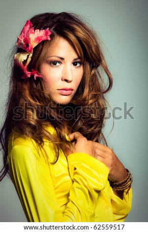 young brunette portrait wearing yellow shirt with bijou flower in hair, vertical orientation, studio shot - stock photo