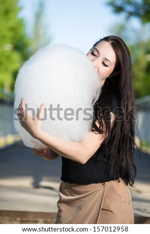 Young brunette posing with a cotton candy - stock photo