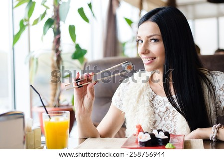 Young brunette pretty woman eating sushi in restaurant and happy smiling - stock photo