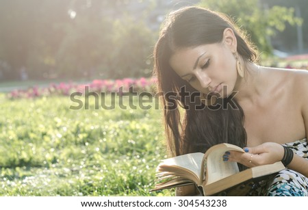 young brunette reading a book in the park
