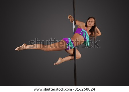 Young brunette  sexy woman exercise pole dance before a gray background - stock photo