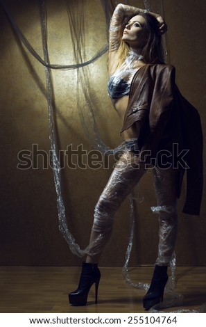 Young brunette sexy woman in a leather jacket and sexy lingerie, wrapped in an oilcloth posing on a gold background. Long legs. Studio shot. The concept of dependence in this world - stock photo