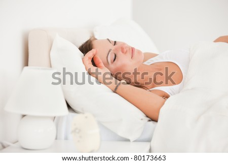 Young brunette sleeping in her bed against a white background