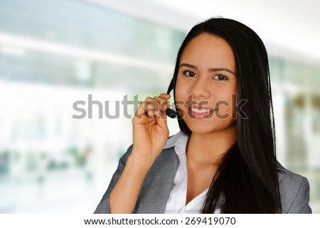 Young brunette smiling and talking on headset