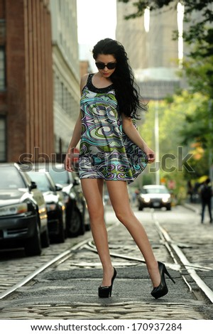 Young brunette standing on old tram rails at Dumbo area in Brooklyn NY