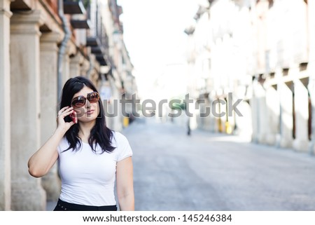 Young brunette talking and waiting in the street