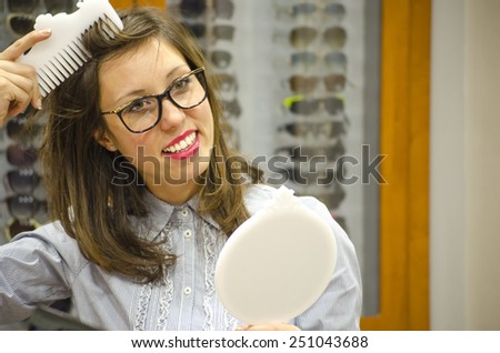 Young brunette trying red glasses at the optics store with different frames in the background - stock photo