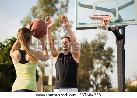 Young brunette trying to score a shot against her boyfriend during a basketball game outdoors - stock photo