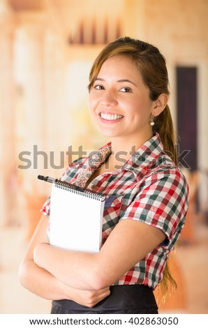 Young brunette waitress wearing uniform standing holding blue plate with friendly smile, restaurant background - stock photo