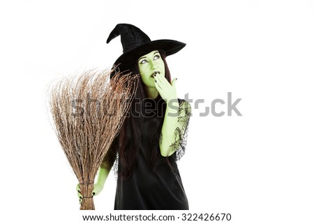 Young brunette witch with broom on a white background - stock photo