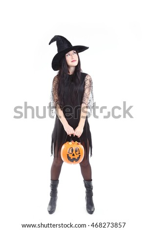 Young brunette witch with pumpkin basket isolated on a white