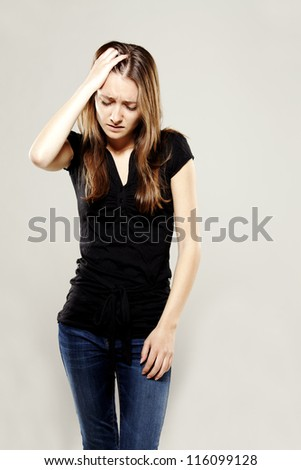 Young brunette with a headache upset about something - stock photo