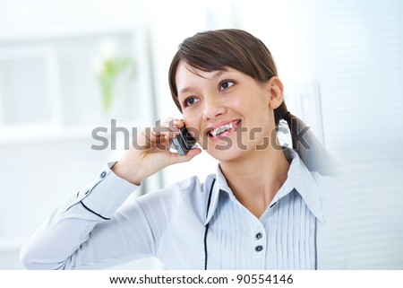 young brunette with glasses smiling talking on cell phone - stock photo