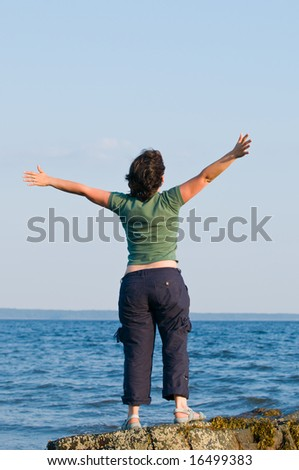 Young brunette woman at the beach, standing on a rock with arms outstretched - stock photo
