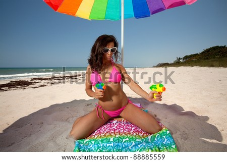 Young Brunette Woman at the beach surfing with squirt guns - stock photo