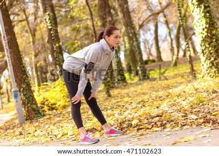 Young brunette woman catching her breath after running in park on sunny autumn day.