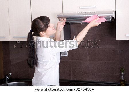 young brunette woman cleaning kitchen - stock photo