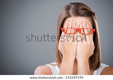 Young brunette woman covering face using her both hands - stock photo