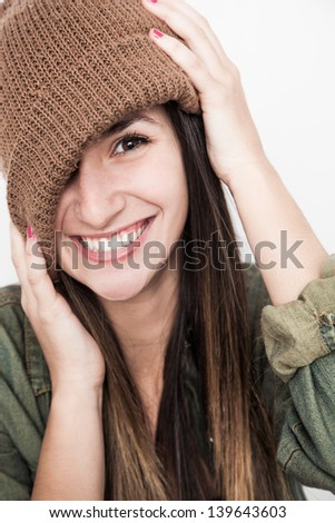 Young brunette woman doing funny face with brown hat