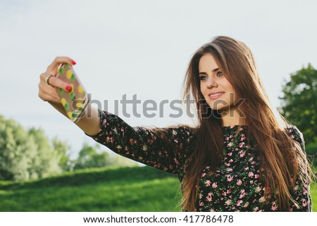 Young brunette woman doing selfie on self phone in park  - stock photo