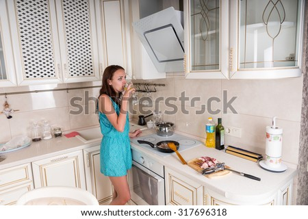 Young Brunette Woman Drinking Wine While Cooking Meat on Stove Top in White Kitchen at Home - stock photo