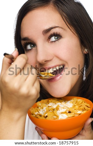 young brunette woman eating corn flakes with yogurt close up