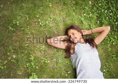 Young brunette woman enjoying the lying on her back on the green grass in the garden. Top view.