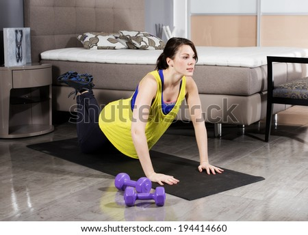 young brunette woman exercising at home in her bedroom