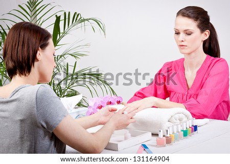 young brunette woman get manicure by professional in beauty salon - stock photo