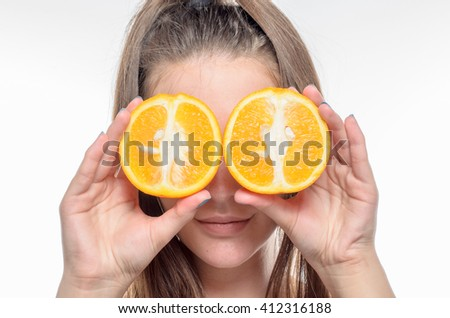 Young brunette woman holding tangerines instead of eyes on white background