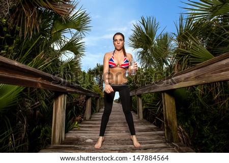 Young Brunette woman in a bikini on a beach boardwalk - stock photo