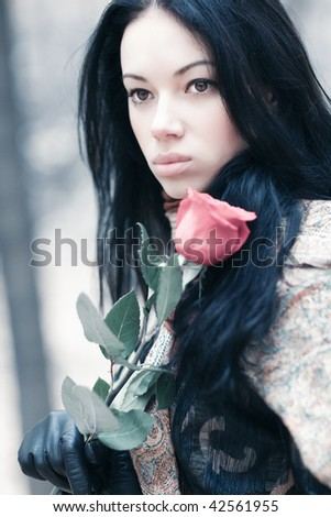 Young brunette woman in a park portrait. IR-style colors. - stock photo