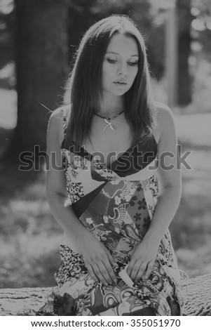 Young brunette woman in a white dress. A girl stands in the middle of pink flowers field on a sunny day. Field, flowers beauty, nature, - The concept of country vacation. Article about vacation.