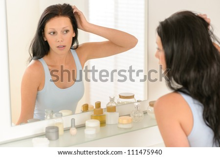 Young brunette woman in bathroom looking at herself in mirror - stock photo