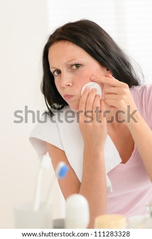 Young brunette woman in bathroom squeezing pimple cleaning acne skin - stock photo