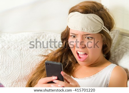 Young brunette woman in bed, comfortably resting on white sheets and pillow, holding mobile phone, surprised facial expression - stock photo