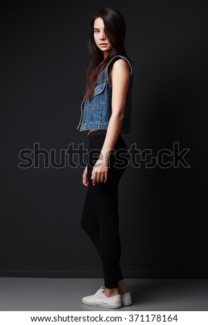 Young brunette woman in denim vest, half turned, gray background