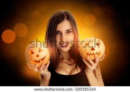 young brunette woman in halloween style with two pumpkins in hands looking at camera in studio