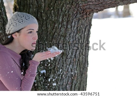 Young brunette woman in knit cap in snow - blowing snow out of hand - stock photo