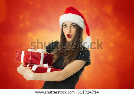 young brunette woman in santa hat with open mouth with red gift in hands on red background