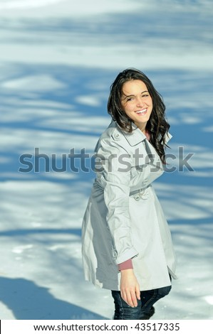 Young brunette woman in snowball fight - follow through - stock photo