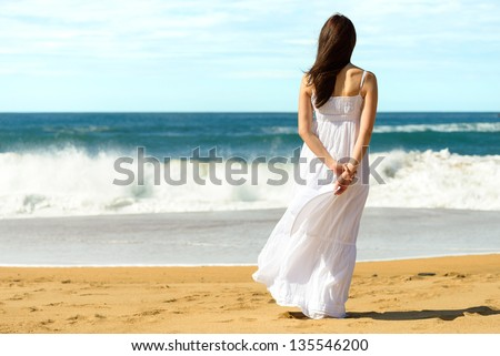 Young brunette woman in summer white dress standing on beach and looking to the sea. Caucasian girl relaxing and enjoying peace on vacation. - stock photo