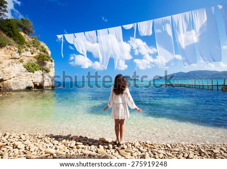 Young brunette woman in summer white dress standing on beach and looking to the sea. Caucasian girl relaxing and enjoying peace on vacation. Greece Island. - stock photo