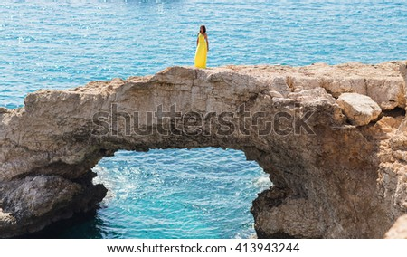 Young brunette woman in summer yellow dress looking to the sea.  - stock photo